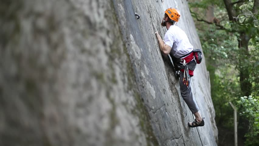 Rock climbing man, climbing with hands, legs and feet on vertical straight wall, very difficult movement. Slow motion 120 fps. Extreme risk outdoor sport. Patagonia Argentina. Trees on the background | Shutterstock HD Video #24682301
