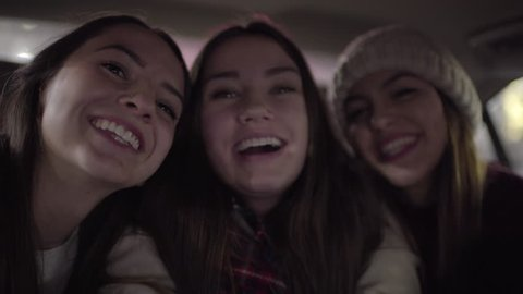 Closeup Of Happy Young Women Making Funny Faces And Cute Faces For Selfies In Backseat Of Moving Car