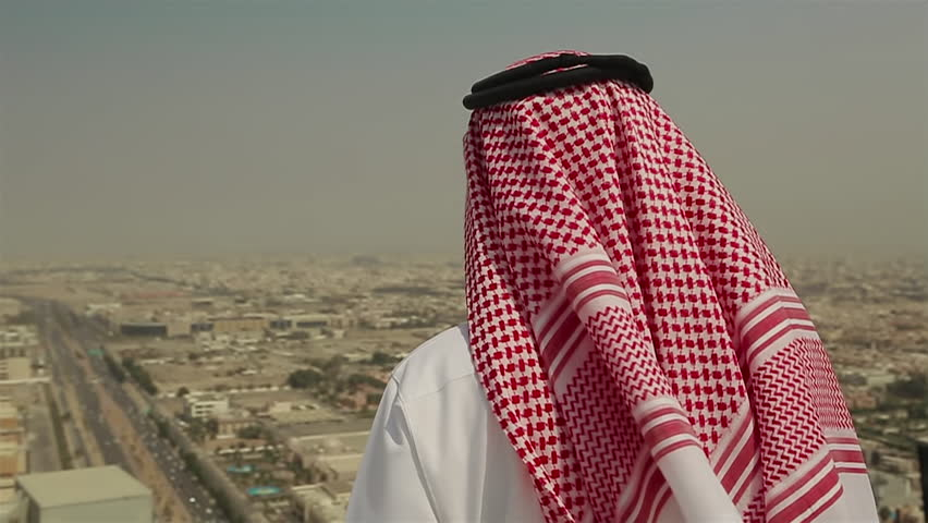 Mid shot of a Saudi Arabian man in local dress standing on a roof looking out across the city of Jeddah, in Saudi Arabia in the Middle East on a windy day.