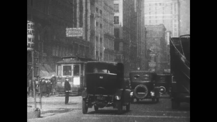 UNITED STATES: 1950s: Motor cars drive through city. Traffic in city street. Balloon Tyres and shock absorbers introduced
