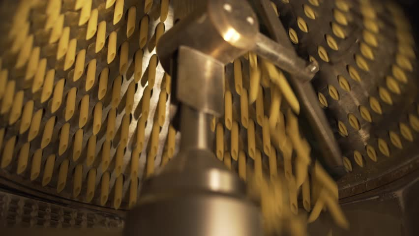 Suggestive shot of raw pasta rigatoni macaroni extruder in a pasta factory. #24714101