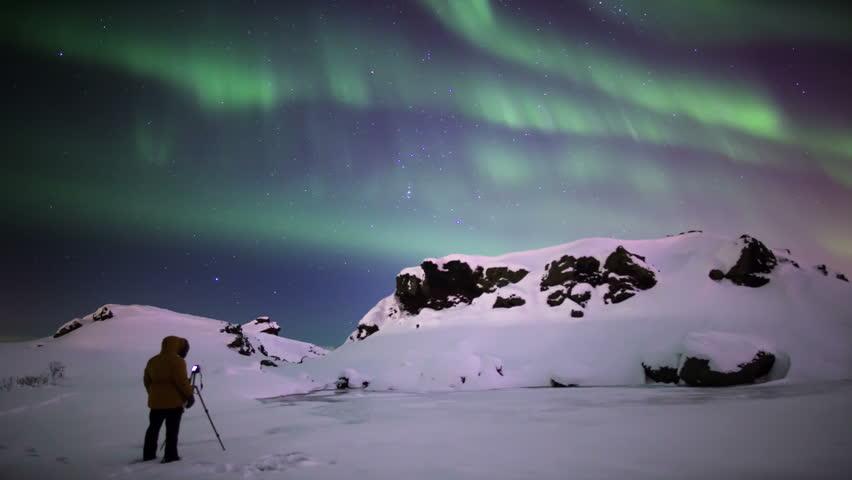Photographer shooting aurora borealis over snowy volcanic terrain Reykjavik Iceland