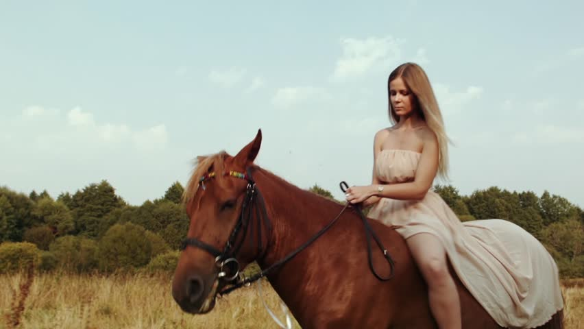 Girl Rides On a Brown Horse In a Meadow. Girl In Dress Riding In The Field. Young Woman Rides On a Brown Horse In a Meadow With Summer Sunlight. Girl With a Horse. Woman On The Horse.