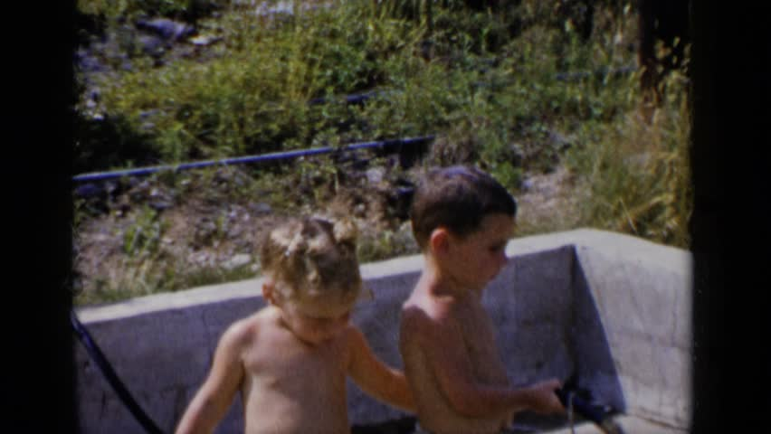 NEW YORK 1951: two children are shirtless, with a drawer and kissing