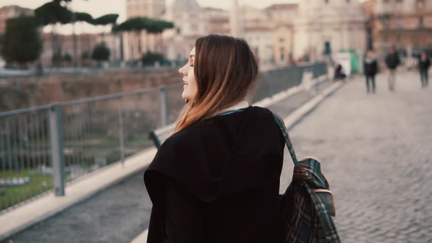 de93cf5279 Brunette woman talking on a phone during walking on a Roman Forum. Girl  tells about the journey in Rome