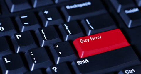 Close up of human finger pushing a Buy Now button with red color on the computer keyboard