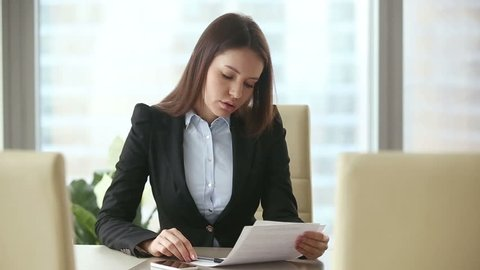 Clients are late or didn't come to meeting. Annoyed businesswoman waiting too long in her office, examining contract with stressed expression, feeling nervous, tapping fingers, checking time on phone