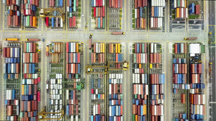 Overhead drone footage of shipping containers with transport network trucks, seamless transport routes supply chain