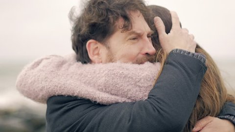 Handsome man crying hugging love of his life