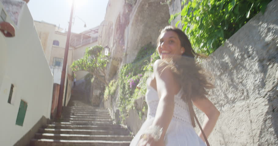 Happy Young Tourist Woman running up through street in Italian town smiling and laughing POV travel concept Amalfi Coast Positano Italy Rear view #24917051