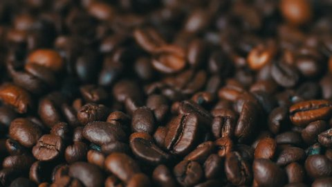 Closeup of coffee beans.Coffee bean shooting in macro. roasted aroma coffee beans over wooden background on Food and Drink theme.Coffee beans background with selected focus