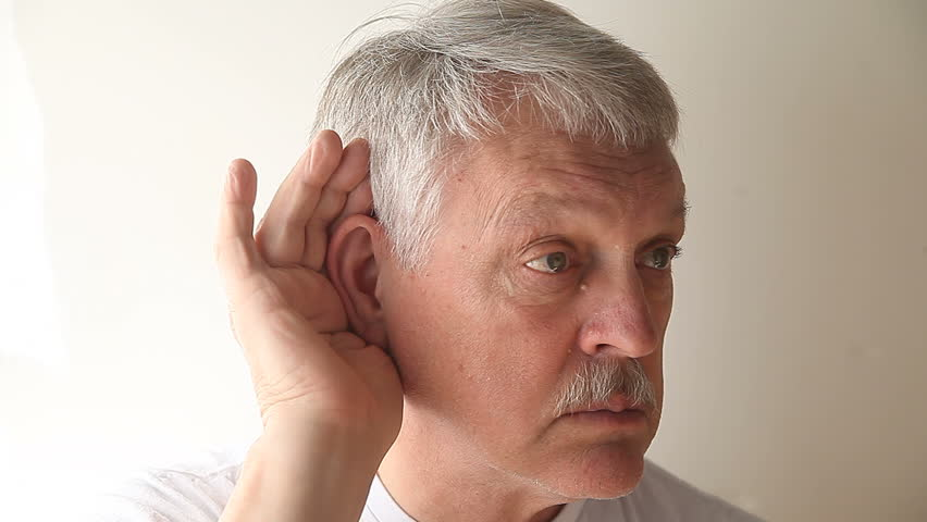 an older man strains to hear what someone is saying