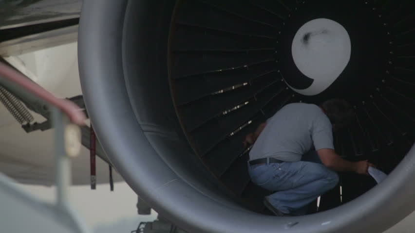 Man checks propeller blades of the turbine engine aircraft