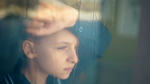 Sad unhappy kid standing near the window. Rain outside the window
