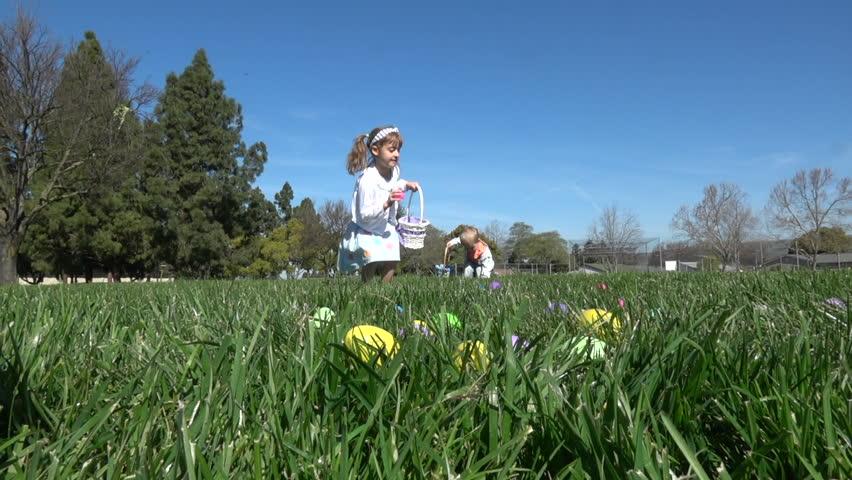 Slow motion of kids having fun gathering eggs at Easter hunt #24973211