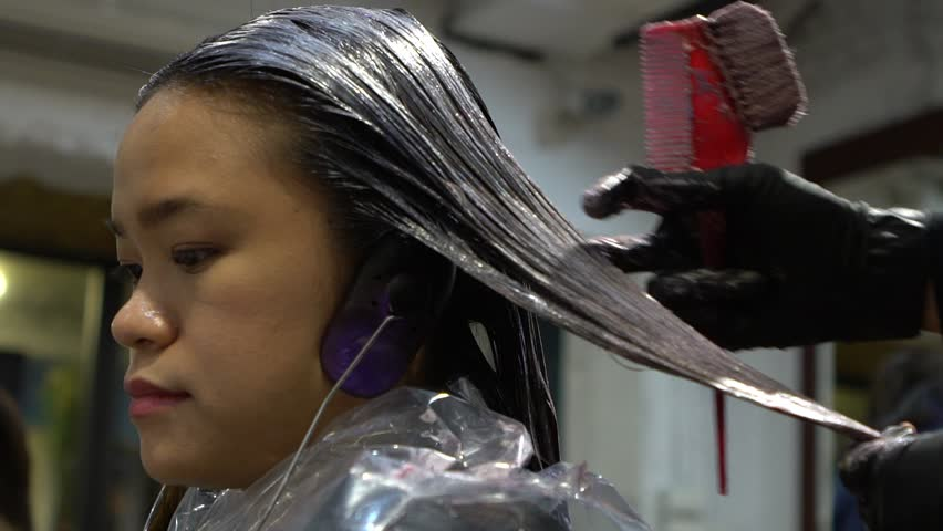 Slow Motion Of Hair Stylist Applying Hair Coloring Dye To Lighten Up ...