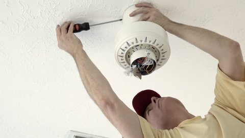 An electrician or homeowner handyman type tightening the screws on the ceiling fan shroud.