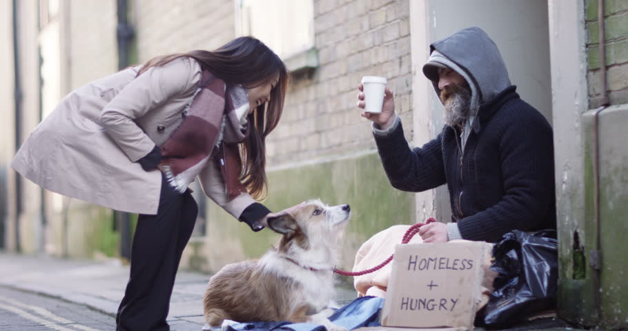 4k, A young woman offering a cup of coffee to a homeless person sitting outside in cold.