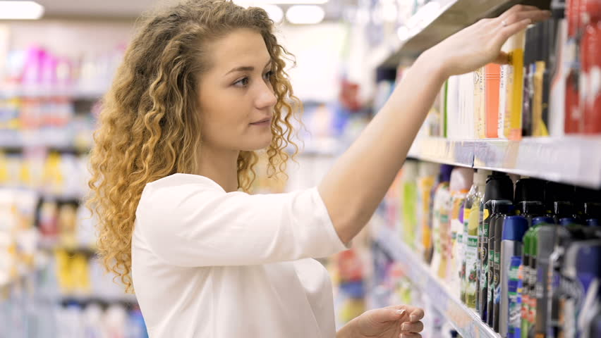Beautiful woman looking at cosmetics in supermarket. Attractive girl buying cosmetic products. Looking and choosing. choosing cosmetic cream in beauty shop | Shutterstock HD Video #25025141
