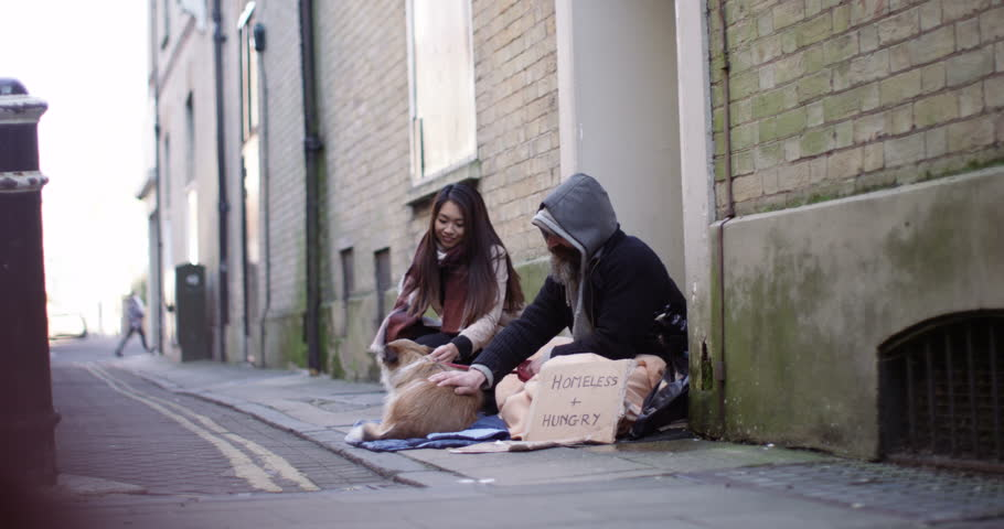 4k, A young woman talking to a homeless person and giving him some money. Slow motion. | Shutterstock HD Video #25027991