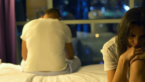 Sad, unhappy couple having sexual problems in bedroom at night