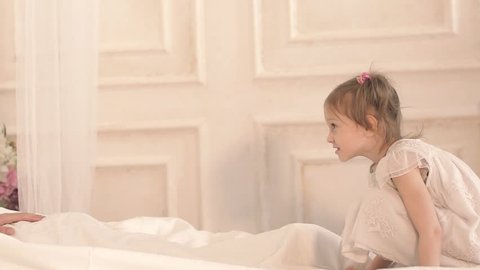 Cute little girl jumping in bed to her father to hug him