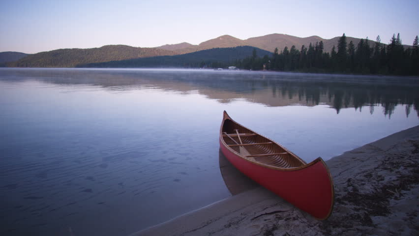 Red canoe on the shore of Priest Lake at sunrise. Mountains and trees reflected in the calm water of the lake.