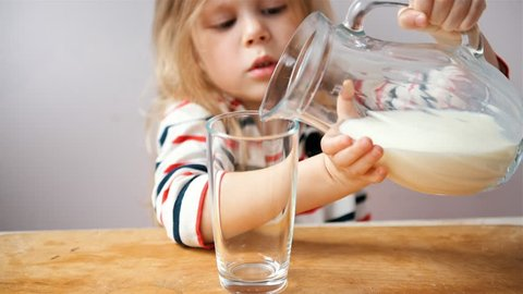 Cute preschooler girl pouring fresh milk into glass sitting at the table in the kitchen.