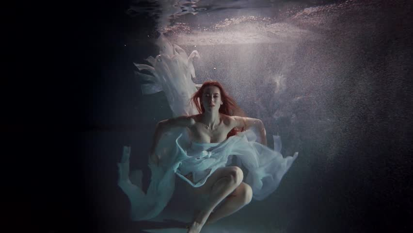 young woman swimming under the water