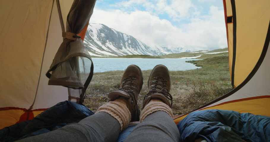 Camping woman lying in tent Close up of Girl feet wearing hiking boots relaxing on vacation POV   Shutterstock HD Video #25063172