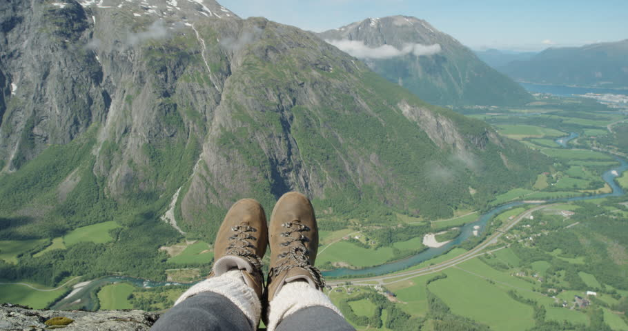 Close up hiking boots of Independent Woman traveller on top of mountain looking at view Hiker girl dangling feet over edge of cliff enjoying vacation travel adventure nature Romsdalen Valley Norway