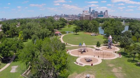 Aerial camera starts over wild flowers and rises revealing playground and Dallas skyline beyond.
