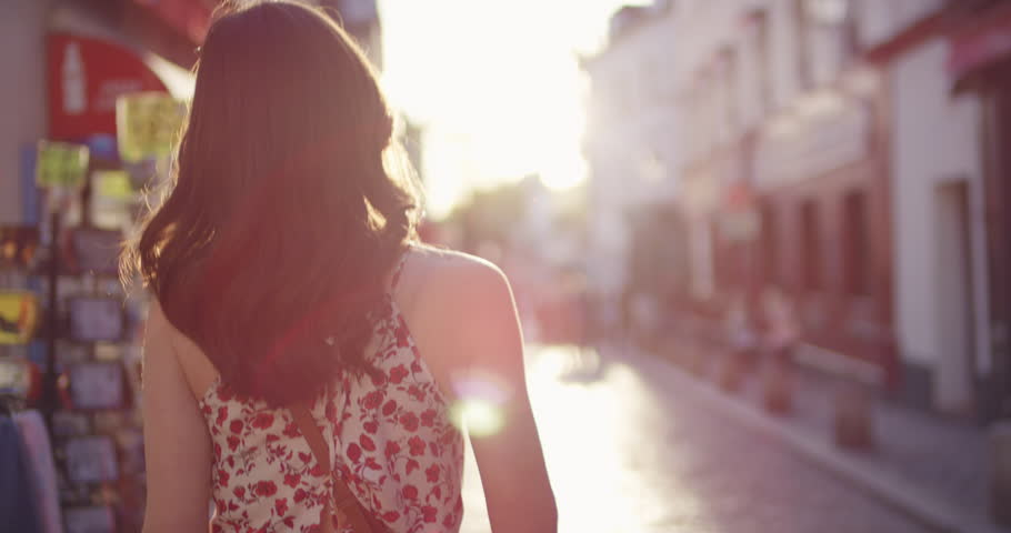 Rear view woman walking through European street at sunset wearing pretty floral summer dress sunshine lens flare confident girl exploring local Paris enjoying holiday travel vacation adventure | Shutterstock HD Video #25098551