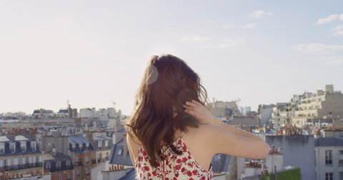 Rear view Woman looking at Paris cityscape background view from rooftop enjoying European vacation travel adventure