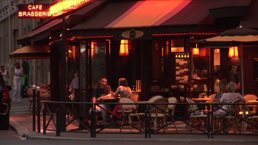 Paris, France - CIRCA June, 2006: People sit at an outdoor table talking and smoking at a cafe during dusk