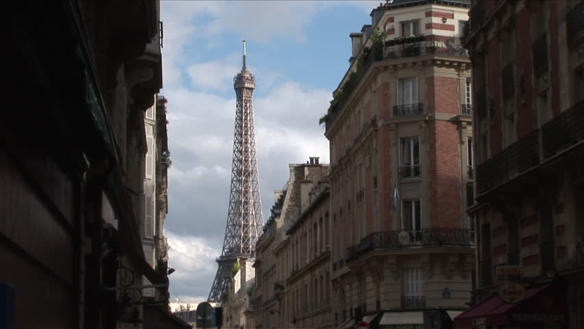 Paris, France - CIRCA June, 2006: View of the Eiffel Tower with a picturesque cloudy sky behind it as seen from the street between some classic buildings