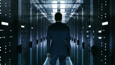 Data Center Technician Walking Through Server Rack Corridor Visually Inspecting Working Server Cabinets. Shot on RED EPIC-W 8K Helium Cinema Camera.
