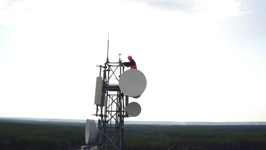 great heights maintenance worker, drone view of telecommunication repeater antenna system, radio master works at great heights of tv or radio tower