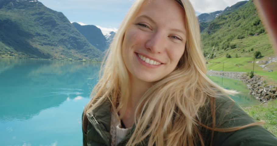 Beautiful woman taking selfie video using smartphone outdoors Girl sharing photograph on social media with mobile phone enjoying Norway  vacation travel adventure | Shutterstock HD Video #25124501