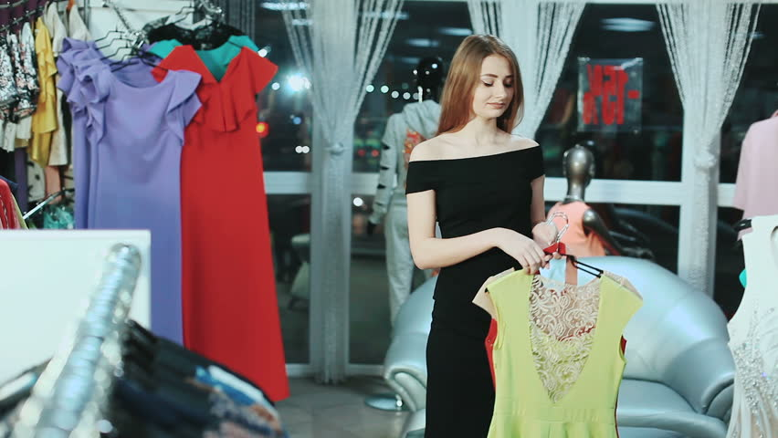Beautiful woman choosing between two dresses. Beautiful woman choosing between two dresses to try them on in mall | Shutterstock HD Video #25135277