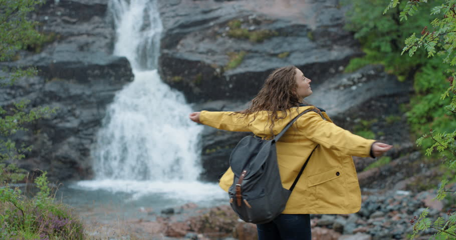 Woman dancing in the rain silly freestyle dance in front of waterfall outdoors Crazy dancer girl having fun enjoying nature celebrating vacation travel adventure