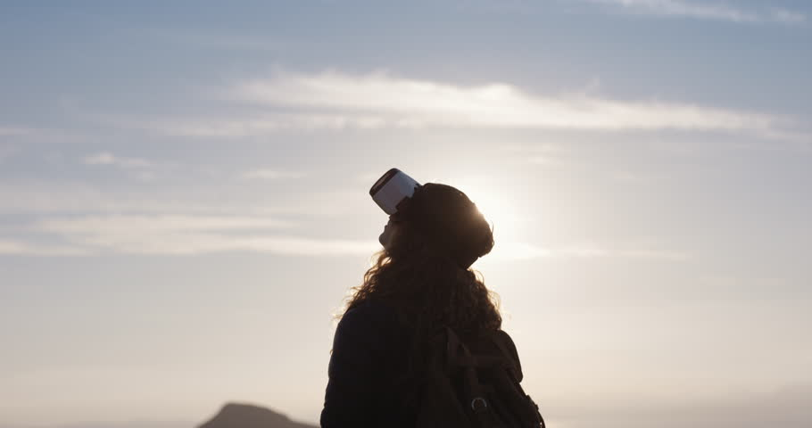 Hiker woman watching sunrise wearing virtual reality headset outdoors mountain top arms outstretched watching 360 video | Shutterstock HD Video #25169531