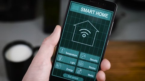 Smart House. Remote home control system on a digital tablet or phone. Men's hands hold a smartphone with an active application for managing the house.
