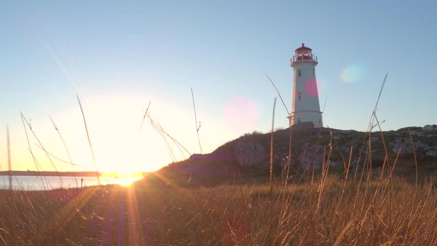 Beautiful Louisbourg Lighthouse standing on rocky and grassy coast rising above North Atlantic Ocean on Nova Scotia peninsula, Canada at golden light sunset. Sunrays illuminating dry straw on seashore