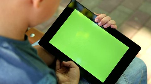 Closeup of handsome blond boy sits on bench in summer or autumn city park. Boy looking at blank green screen of modern tablet pc. Real time full hd video footage. View from above.