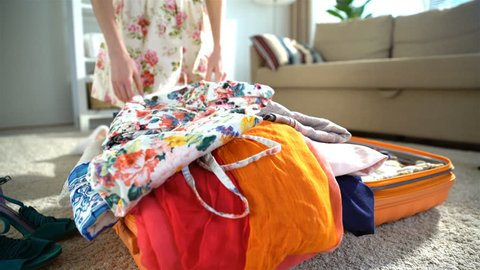 A young woman is trying to close the chock-full orange suitcase.