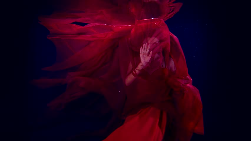 Slow motion dancing girl artist under water. For a red cloth to the light with his hands and face. | Shutterstock HD Video #25201607