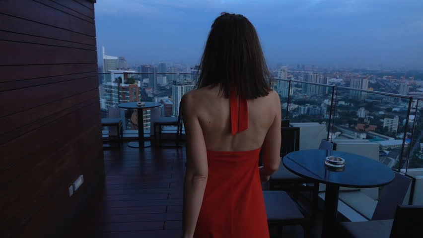 Elegant, young woman walking on terrace in bar, super slow motion 240fps