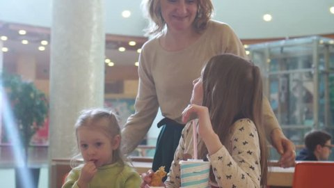 Cute little kid girls portrait funny eating in fast food court in a mall