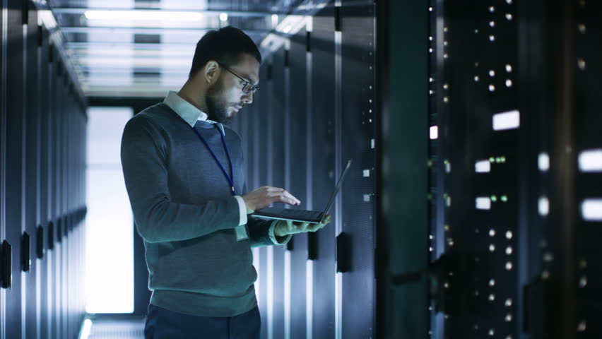 Male IT Technician Working on a Laptop Standing Before Open Server Rack Cabinet in Big Dara Center. Shot on RED EPIC-W 8K Helium Cinema Camera. | Shutterstock HD Video #25243031